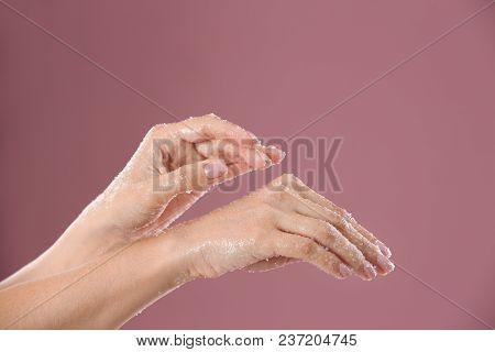 Young Woman Applying Natural Scrub On Hands Against Color Background