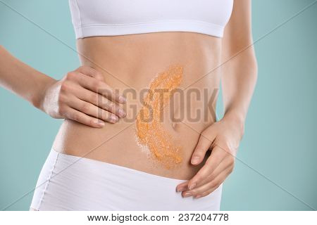 Young Woman Applying Natural Scrub On Her Belly Against Color Background, Closeup