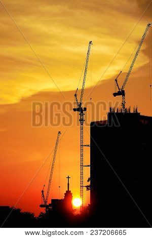 Sunset Silhouette Construction Building Tower Crane Cross On The Roof Of The Church Of The Sloane