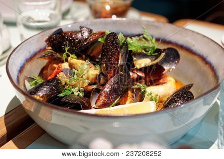 Cooked mussels in a deep clay bowl with turmeric sauce and lemon