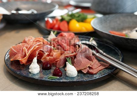 Assortment of cured and smoked meats and roast beef on stone plate