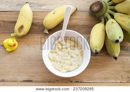 Mashed Banana Healthy Foods For Baby On Background Wooden