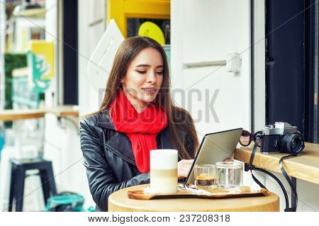 Portrait Of A Young Beautiful Woman In A Street Cafe . The Girl Is Resting After A Walk Around The C
