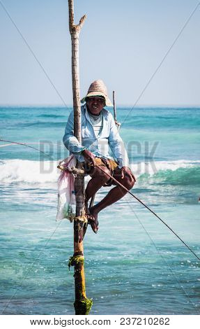 WELIGAMA SRI LANKA - JAN 6, 2017: Unidentified local fishermen are fishing in unique style, sitting on sticks in Weligama on Jan 6, 2017. Sri Lanka. This type of fishing is traditional for Sri Lanka .
