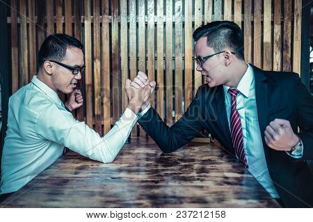 Two Asian Businessman Expressed A Serious Expression And Fighting By Used Arm Wrestling On Wood Tabl