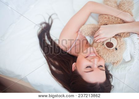 The Girl Woke Up In A White Bed In The Morning. In The Hands Of Holds Bear