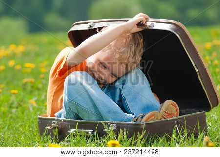 Cute Little Funny Child Trying To Hide Inside Of Vintage Brown Suitcase. Boy Laughs And Smiles Happi