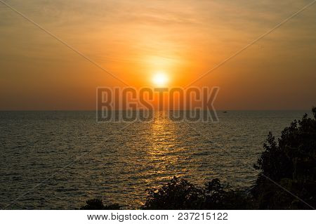 Orange Sunset Landscape With Sea And Trees. Vivid Orange Sunset Sky. Romantic Evening Seascape With