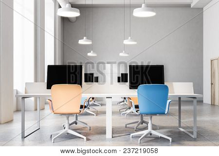 Orange And Blue Chairs Open Office Interior With A Conrete Floor, Rows Of Computer Desks And Blue An