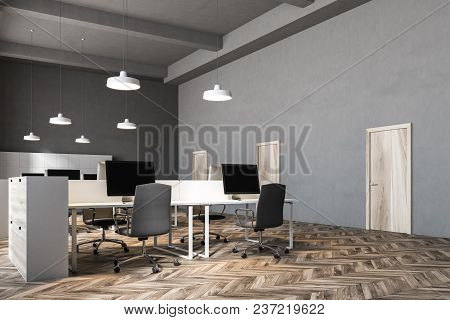 Black Chairs Open Office Corner With A Wooden Floor, Rows Of Computer Desks And Black Office Chairs