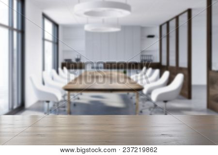 White Boardroom Interior With A Concrete Floor, Loft Windows, A Long Wooden Table And White Chairs.