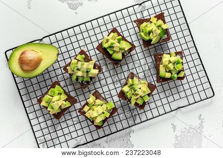 Healthy Avocado rye sourdough toasts with sesame seeds, drizzled with olive oil and sea salt flakes poster