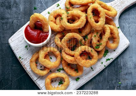 Fried Onion Rings With Ketchup On White Cutting Board