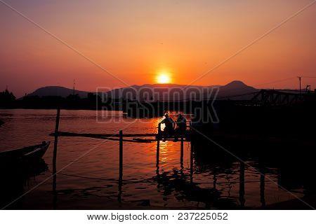 Sunset Time On River. Orange Sunset Landscape With Pier And Men. Vivid Orange Sky View. Romantic Eve