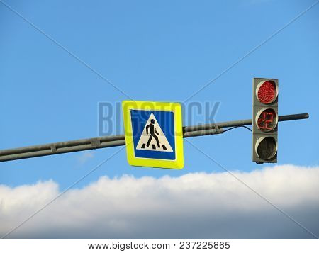 Pedestrian Crossing Sign And Red Traffic Light On Blue Cloudy Sky Background. Forbidden Path Concept