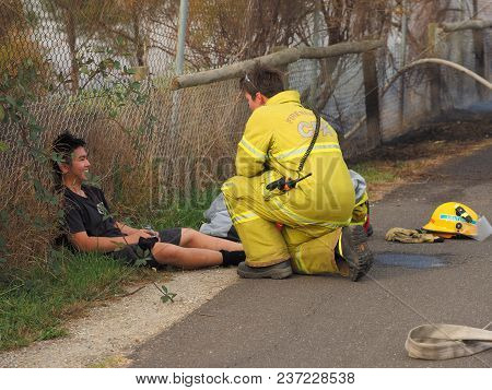 Melbourne, Australia - April 13, 2018: Fire Fighter Attend To A Peer Without Uniform During A Bush F