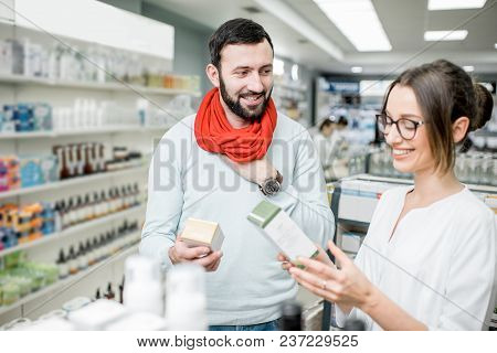 Pharmacist Helping To Choose Medications For The Man Suffering From Cold Standing In The Pharmacy Su