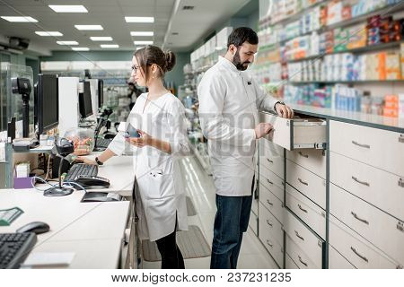 Man And Woman Pharmacists Working At The Cash Register Of The Modern Pharmacy Store