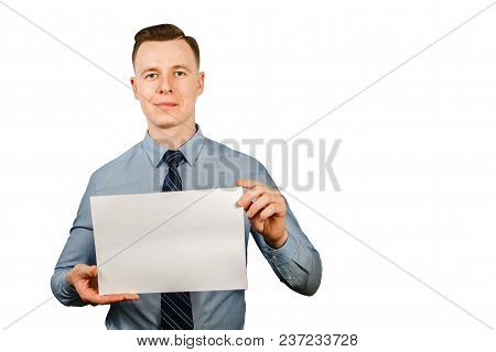 Young Businessman Dressed In Blue Shirt And Tie Holding Blank Blank Sheet Of Paper A4, Isolated On W