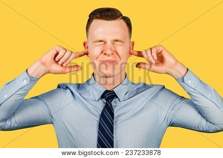 Young Businessman Dressed In Blue Shirt And Tie Closing His Ears And Eyes, Isolated On Yellow Backgr