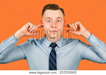 Young Businessman Dressed In Blue Shirt And Tie Closing His Ears, Isolated On Red Background.