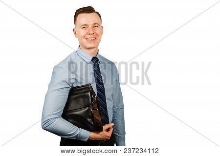 Young Businessman Dressed In Blue Shirt And Tie Holding A Briefcase Under His Arm, Isolated On White