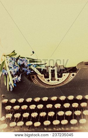Old Antique Black Vintage Typewriter With Blue Romantic Spring Flowers.