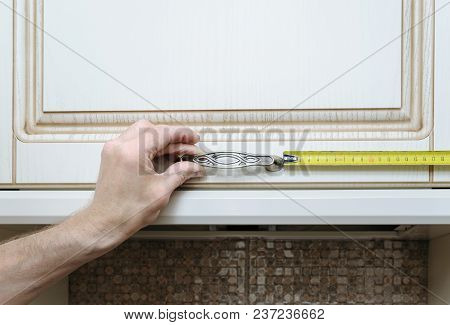 Installation Of Kitchen Furniture. A Man Is Measuring Distance Where To Fix Door Handle Cabinet.