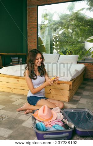 Attractive Asian Young Woman Packing A Travel Bag Before Going On Holiday. Life Style Concept.