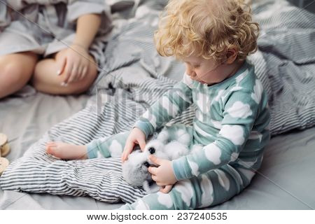 Little Curly Baby Boy In A Cute Suit Is Sitting On The Bed And Playing With A Soft Toy
