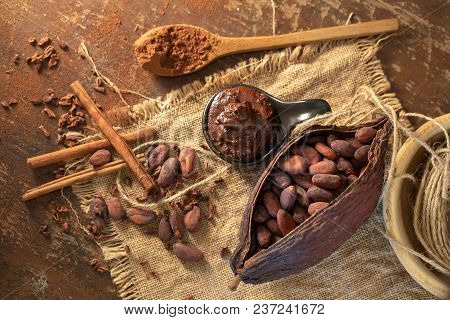 Cocoa Pod ,beans And Cocoa Nibs Setup On Rustic Wooden Background