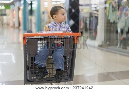 Baby Boy Rides In A Trolley Through A Shopping Center