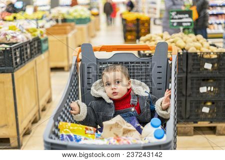 Boy 2 Years In A Supermarket, Sitting In A Cart Full Of Various Products.