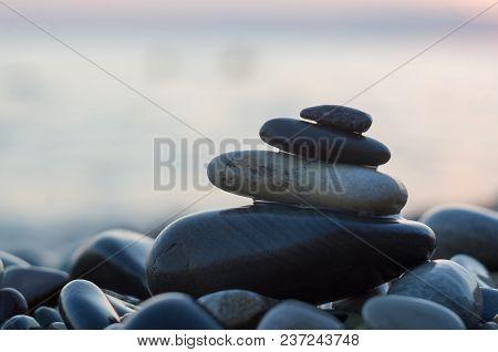 Folded Pyramid Zen Pebble Stones On The Sea Beach At Sunset