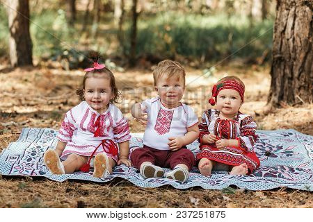 Three Children In Traditional Ukrainian Shirts Sits On Ground In Spring Forest. Vyshyvanka Style.