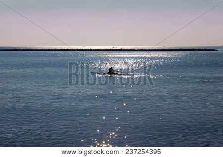 Silhouette Of Kayaker Man In The Backlight Of Sun. Glare Of The Sun On The Blue Water Like Stars In