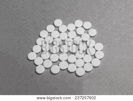 Black And White Photo Of A Pile Tablets On Cardboard Paper