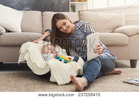 Happy Beautiful Business Mom Using Digital Tablet While Her Cute Baby Playing With Toys In Cradle, S