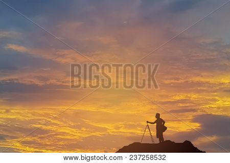 The Silhouette Of A Photographer Preparing To Shoot The Sun At Sunset. At The Top Of The Mountain