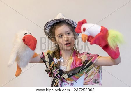 Girl 8 Years In A Hat Playing Rag Dolls. Puppet Show. Crow And Cock. Creative Toys.