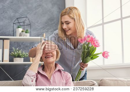 Daughter Closing Mother's Eyes And Giving Flowers