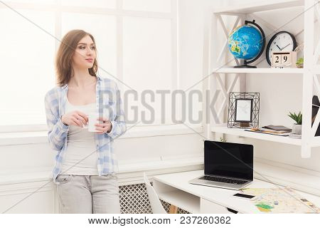 Young Pensive Woman Dreaming About Traveling Around World, Looking At Globe, While Having Coffee Bre