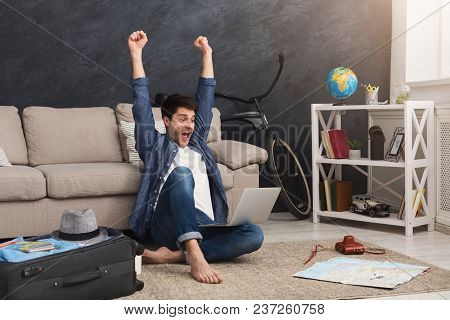 Excited Man With Laptop Celebrating Lottery Win Of Travelling, Planning Route Of Vacation, Sitting W