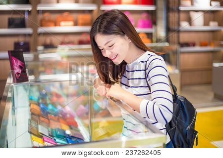 Happy young attractive asian woman shopping and looking at merchandises in glass display cabinet at a shop deciding which one to buy poster