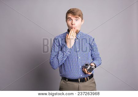 Portrait Of Amazed Man Covering His Mouth Over Gray Background.