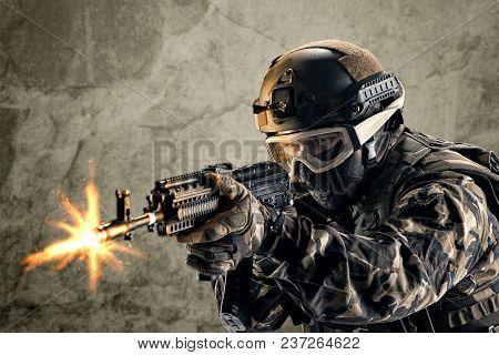 Special Forces Soldier With Guns On Concrete Background.