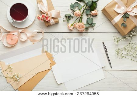Wedding Invitations And Craft Envelopes On White Wooden Background. Top View On Paper Cards, Rings A