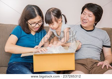 Portrait Of Asian Little Girl With Her Parents Unpacking Boxes Together, Asian Family Moving House U