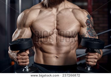 Athlete Muscular Bodybuilder  With Dumbbells .fitness Concept Background.