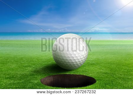 Golf Ball On Edge Of The Hole. Shallow Depth Of Field. Focus On The Ball And The Hole.